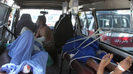 Injured Afghan men lie in an ambulance after a deadly road accident in Afghanistan Sunday.