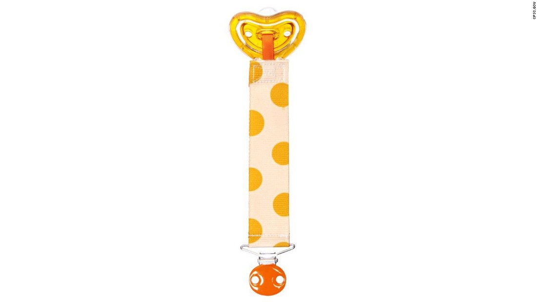 The designer pacifiers and clips 0-months-plus and 6-months-plus are in three color patterns: blue and white strips, orange and with white polka dots and pink with white polka dots.