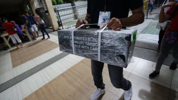 An election worker carries official ballots as they are distributed to polling centers in the suburban Quezon City, north of Manila on May 8, 2016.