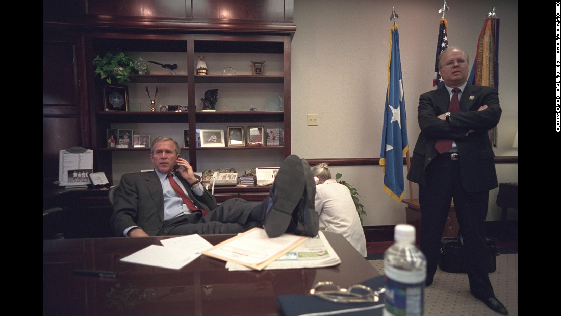 Bush talks on the phone at a Louisiana Air Force base as adviser Karl Rove stands by.