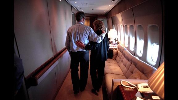 Bush and White House Staff Secretary Harriet Miers walk through Air Force One en route to Washington.