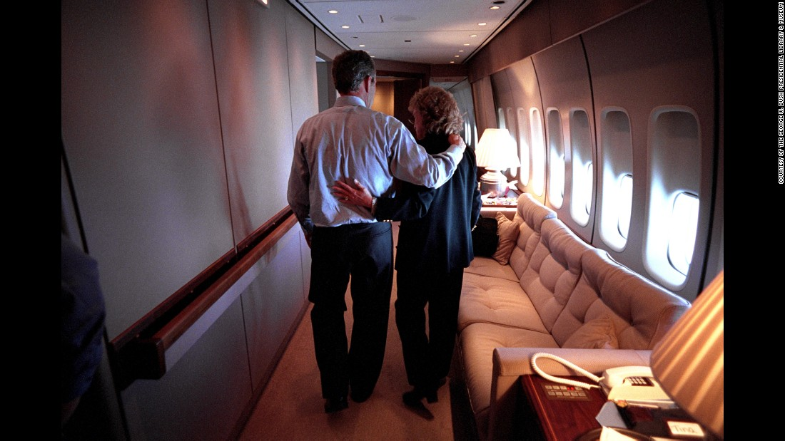 Bush and White House Staff Secretary Harriet Miers walk through Air Force One en route to Washington.