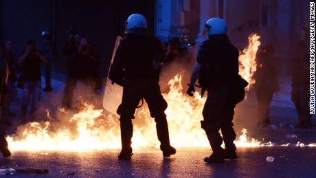 Police stand guard as protesters throw molotov cocktails at an anti-austerity protest in Athens, May 8, 2016.