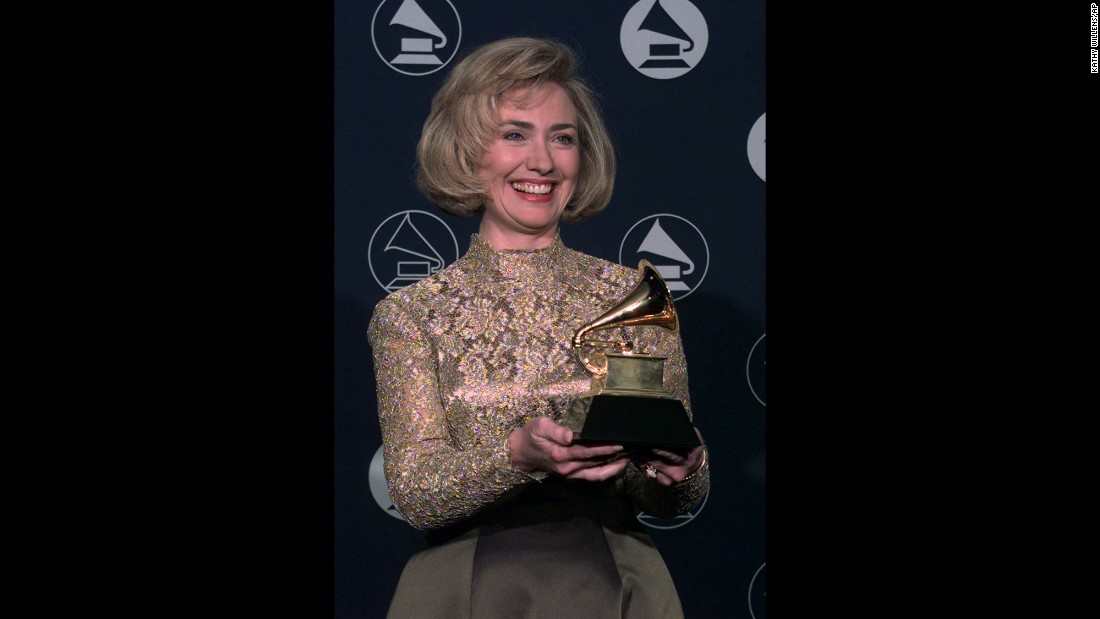 "The first lady holds up a Grammy Award, which she won for her audiobook ""It Takes a Village"" in 1997."