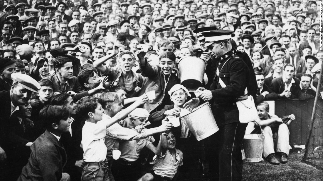 Three years later, St John's Ambulancemen hand out oatmeal drinks in the heat at the match between West Ham and Tottenham Hotspur at Upton Park.