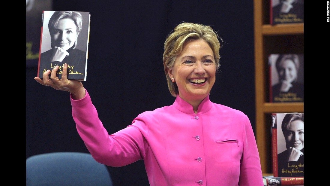 "Clinton holds up her book ""Living History"" before a signing in Auburn Hills, Michigan, in 2003."