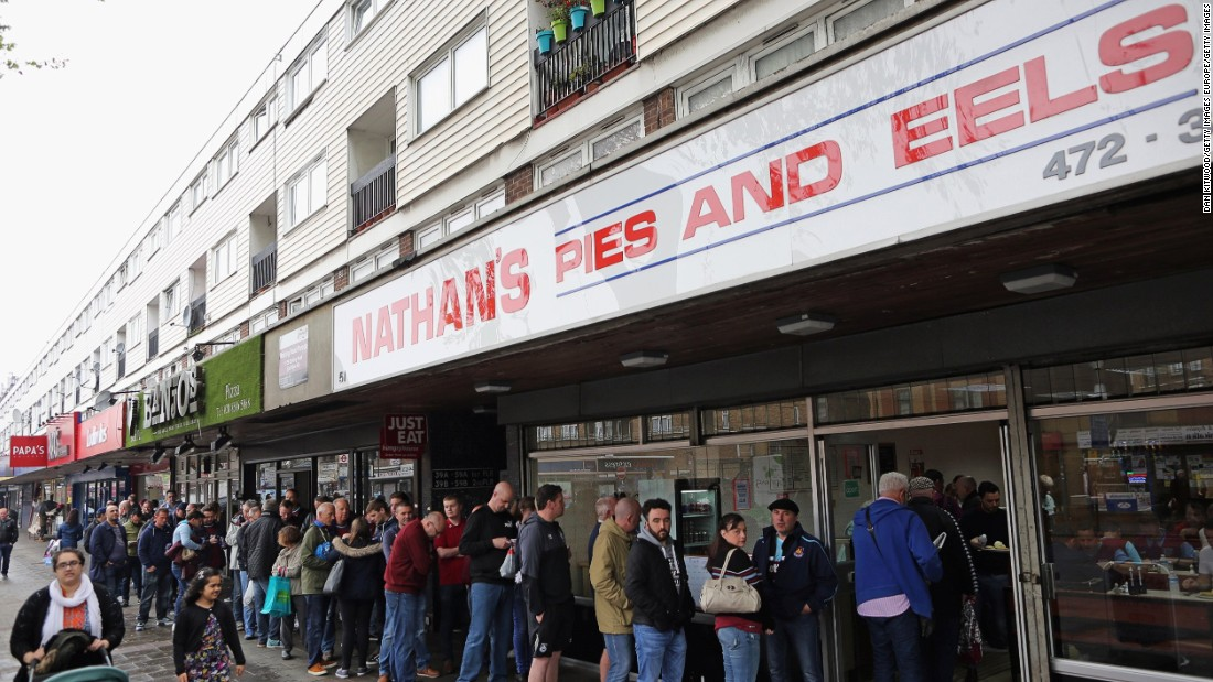 Hammers supporters queue outside a cafe serving traditional East End fare: Pie and eels.