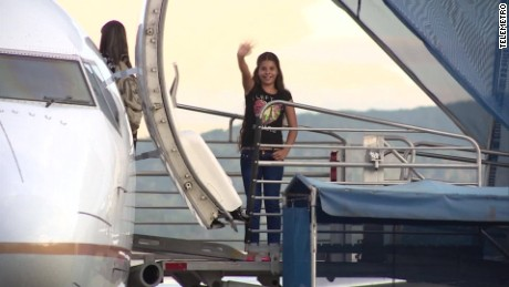 A Cuban girl waves goodbye as a group of Cubans, stranded in Panama for months on their way to the U.S., depart the Panama City airport bound for northern Mexico on May 10, 2016.