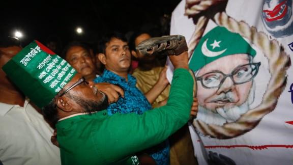 A Bangladeshi man throws a shoe at a poster of Motiur Rahman Nizami following the Jamaat-e-Islami party leader's execution.