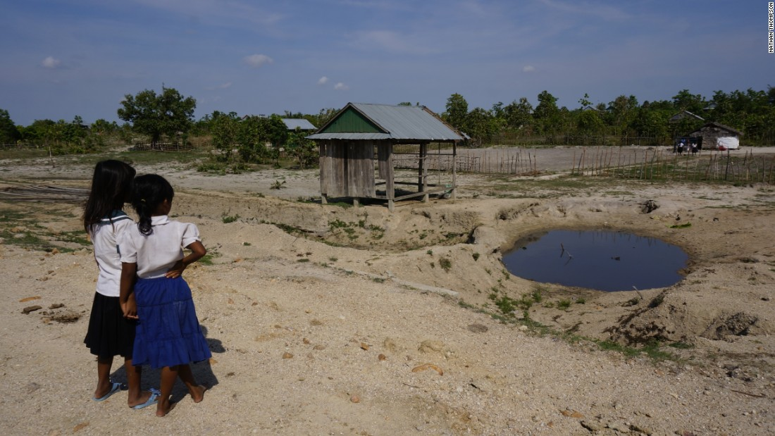 Two schoolgirls look at a stagnant pond. They have no choice but to wash in it and often suffer skin conditions and risk malaria as a result.