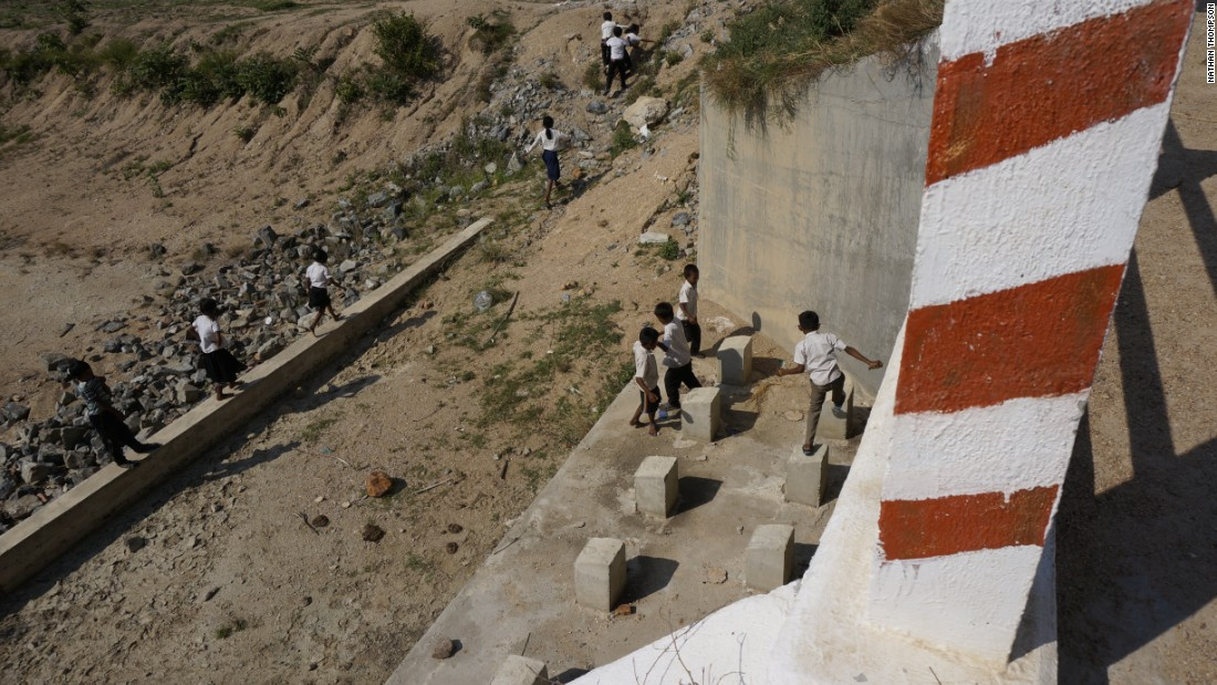 Children play in a dry riverbank in front of a dam. Even if the gates were opened, no water would flow out.