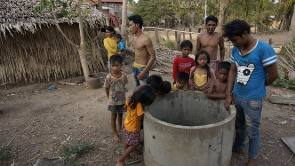 A community gathers around a dry well. The children have been kept home because it's too hot to go to school and they are needed to collect water from wells further afield.