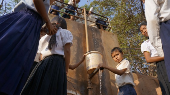 Children pump water in Tbong Khmum, Cambodia. The well is one of the few working wells left and the water has to be carefully rationed.