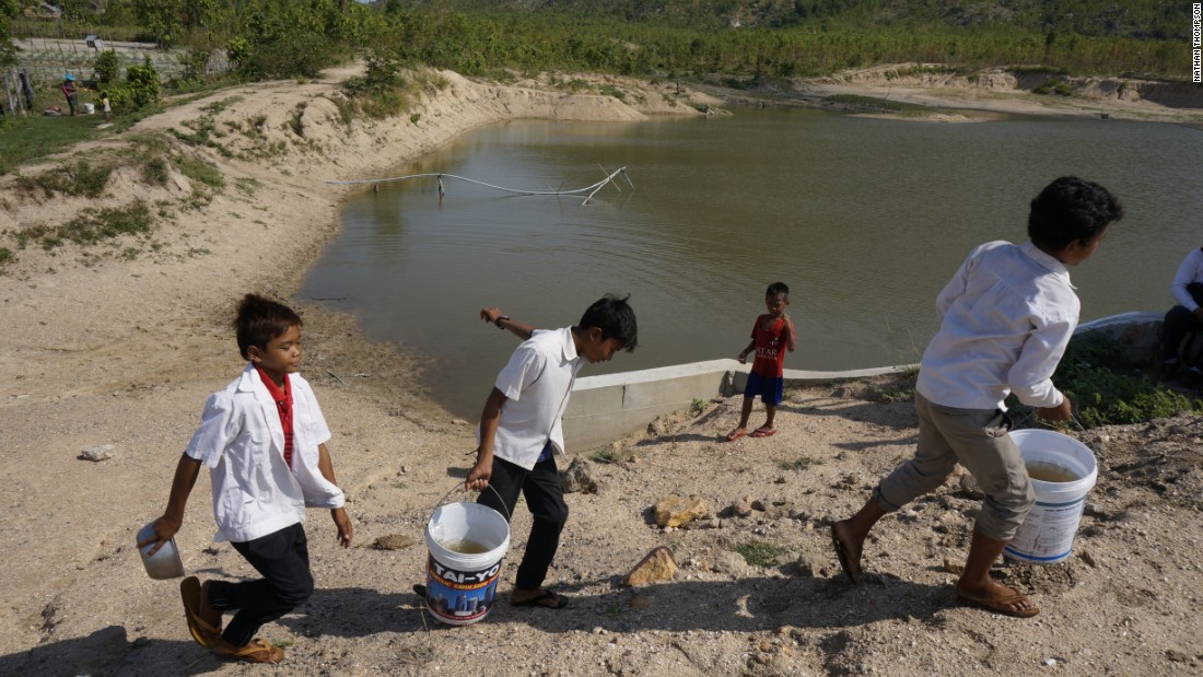 Three boys carry buckets of stagnant water for use in the school latrines.