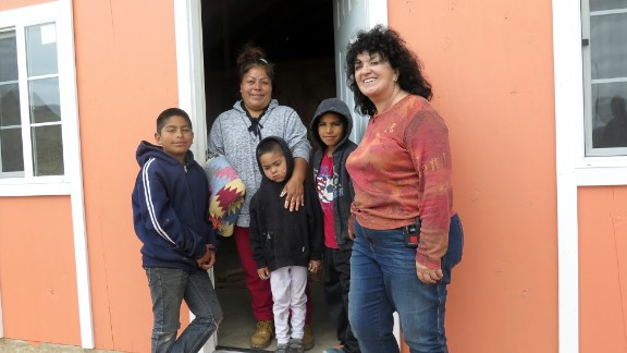 Claussen stands outside a Project Mercy home with the Cervantes family