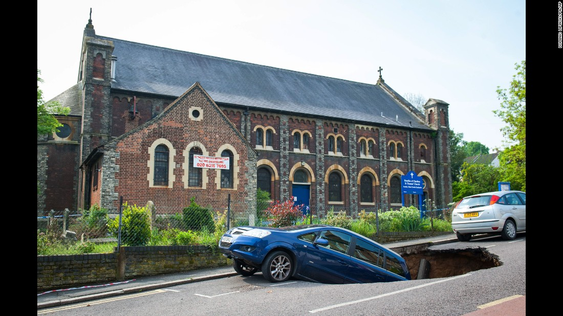A car hangs on the edge of a sinkhole in London on Thursday, May 12.