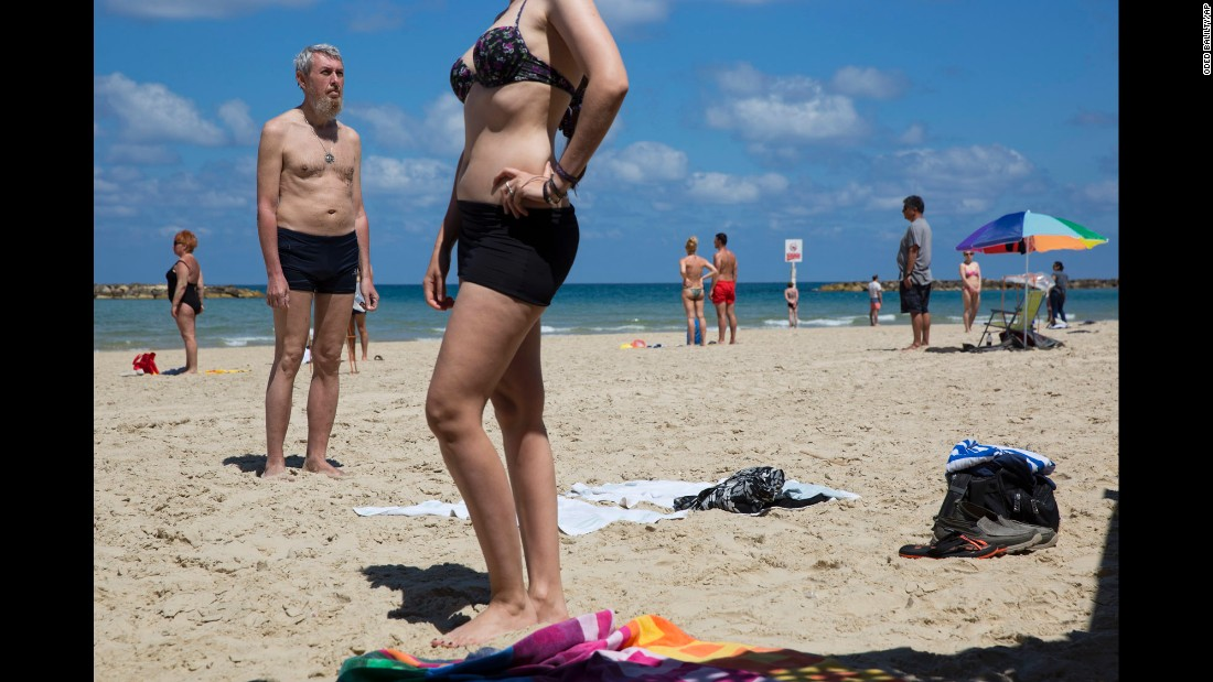 People stand still on a beach in Tel Aviv, Israel, as they observe two minutes of silence for fallen soldiers on Wednesday, May 11. It was the country's annual Memorial Day.