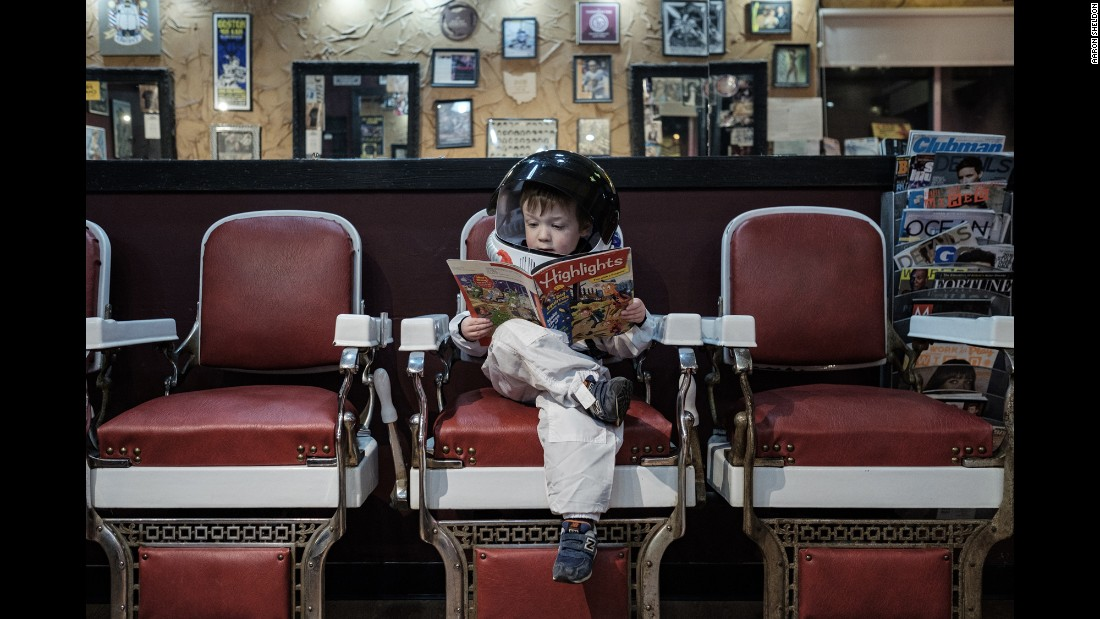 "Aaron Sheldon's son, Harrison, reads a magazine inside a Columbus, Ohio, barbershop. He is wearing an astronaut costume for Sheldon's project ""Small Steps Are Giant Leaps,"" which illustrates how children -- like astronauts -- are constantly exploring the world around them."