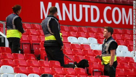 A sniffer dog patrols the Old Trafford stands.