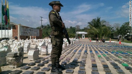A handout picture released by the Colombian Police shows a Colombian Police officer standing guard in front of a display of confiscated packages of cocaine in Turbo, Colombia, 15 May 2016. At least eight-tons of cocaine was seized by the Colombian police, the biggest cargo confiscated in the history of the country, according to Colombian President Juan Manuel Santos. The drugs belonged to the major criminal gang of Colombia, the 'Clan Usuga', the Ministry of Defense reported.