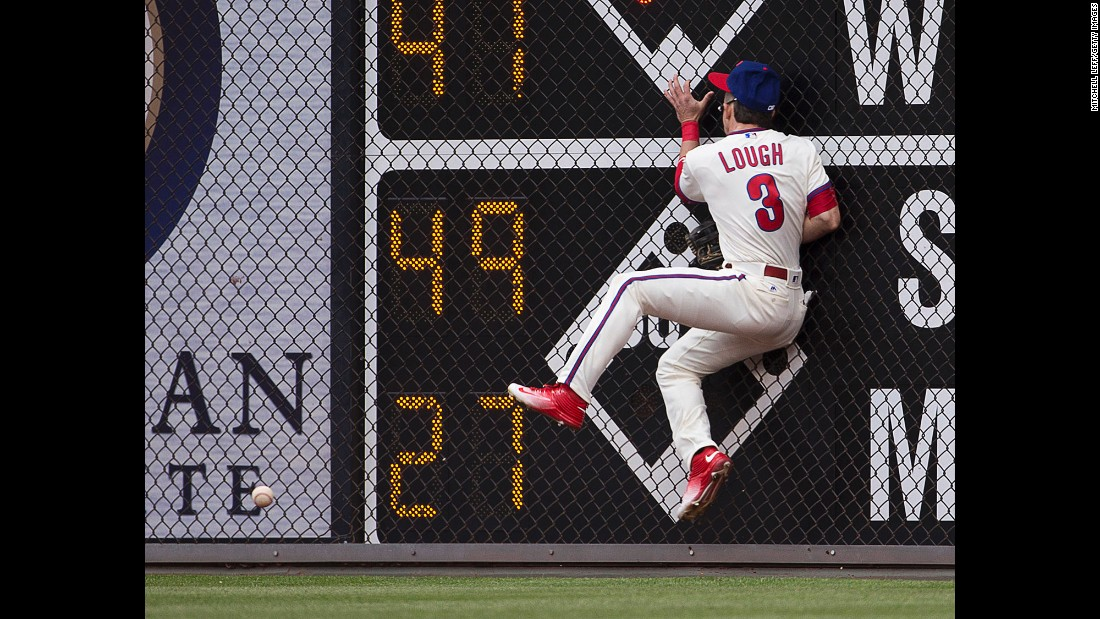 Philadelphia's David Lough crashes into the outfield wall as he tries to make a catch during a home game on Sunday, May 15.