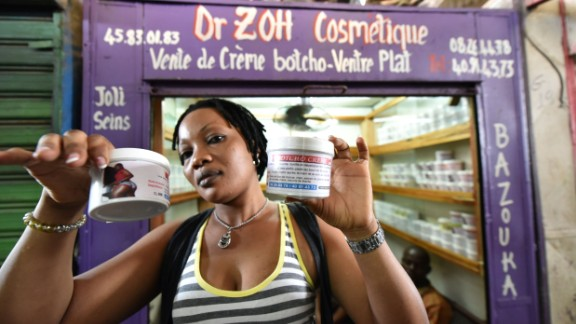 A shopkeeper in a market in Abidjan shows pots of cream thought to help enhance bottoms. The cream's label says it's made of cod-liver oil, honey or shea butter.