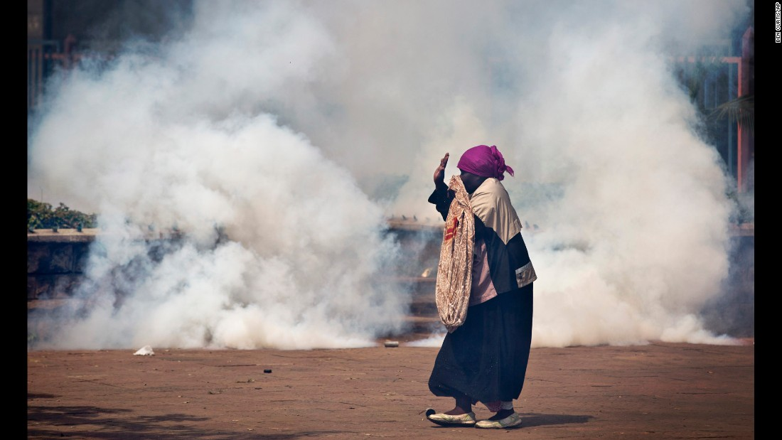 An elderly woman caught up in the clashes holds her hands in the air as a riot policeman approaches amid clouds of tear gas.
