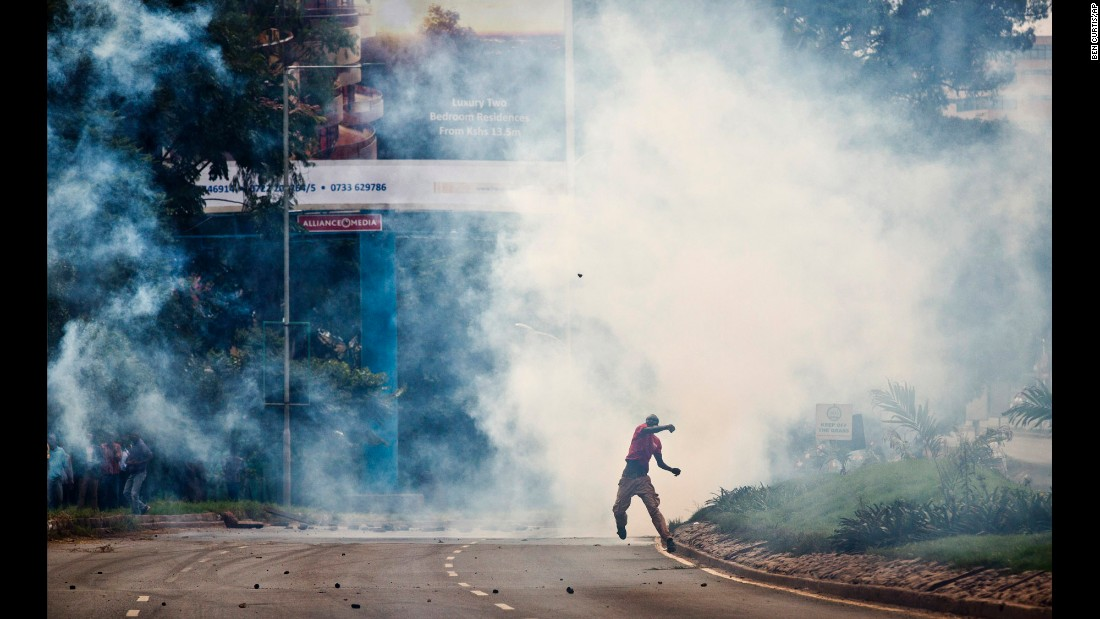 "An opposition supporter standing amid clouds of tear gas throws a rock toward riot police during a protest May 9. Curtis said, ""Many are hoping that some kind of political resolution of this issue can occur before the protests get further out of hand, but so far there are not many promising indications."""