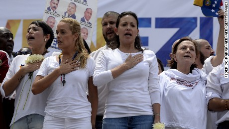 (L-R) San Cristobal's Mayor Patricia de Ceballos, wife of the imprisoned former mayor of San Cristobal, Daniel Ceballos, Lilian Tintori, wife of jailed opposition leader Leopoldo Lopez, Venezuelan opposition leader Maria Corina Machado and Mitzy Capriles, wife of Venezuelan opposition leader Antonio Ledezma -- currently under house arrest -- sing the national anthem during a peaceful demonstration against the government of Venezuelan President Nicolas Maduro, in Caracas, on May 30, 2015. The protesters are demanding the release of political prisoners, including that of Lopez, who called the demonstration and is on a hunger strike.  AFP PHOTO / FEDERICO PARRA        (Photo credit should read FEDERICO PARRA/AFP/Getty Images)