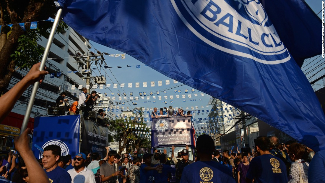 Fans wave a giant flag as Leicester's football players and owners parade through the streets of Bangkok on an open-top bus.