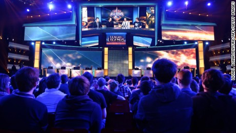 "Visitors listen to commentators after a battle between international teams during the tournament of the computer game ""League of Legends"" on May 8, 2014 in Paris."