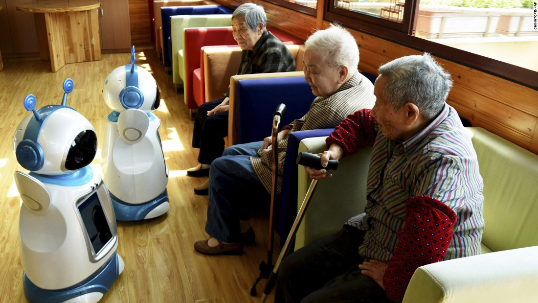 Retirees look at Ah Tie robots at a nursing home in Hangzhou, China, on Tuesday, Nay 17. The robots were designed for nursing homes and are capable of monitoring vital signs. They can also be used for video conferencing.