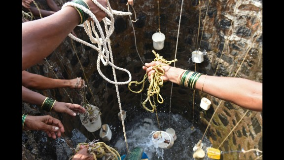 Villagers in Shahapur throw containers into a well on May 13.