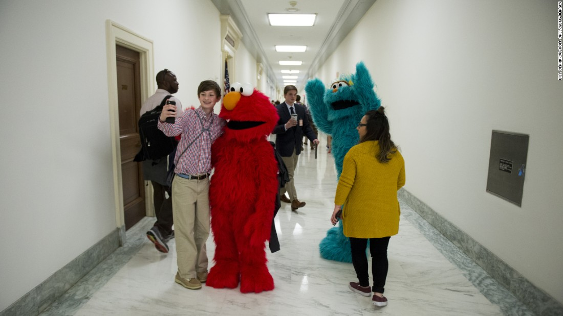 """Sesame Street"" characters Elmo and Rosita pose with visitors in the halls of the Rayburn House Office Building after attending a USO event in Washington on Tuesday, May 17."