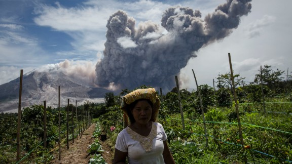 Smoke from Mount Sinabung billows behind a woman in June 2015.
