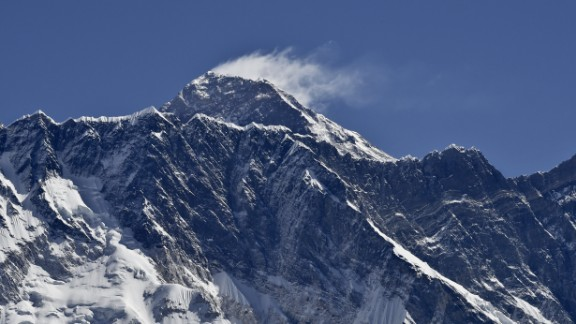 This photograph taken on April 20, 2015 shows a view of Mount Everest (C-top) towering over the Nupse, from the village of Tembuche in the Khumbu region of northeastern Nepal.  Sherpas, thought to be of Tibetan origin, have a long and proud history of mountaineering, and the term today is used for all Nepalese high-altitude porters and guides assisting climbing expeditions around Everest. The April 25 quake, which left more than 7,800 people dead across Nepal, was the Himalayan nation