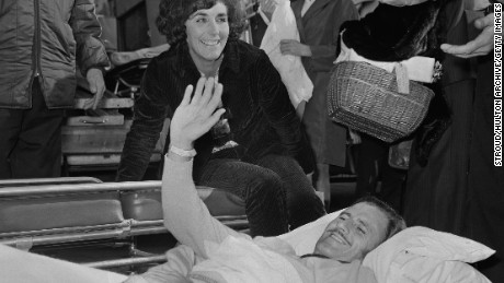 Oct 1969: An incapacitated Hill returns home to the UK from the U.S. alongside wife, Bette (C).