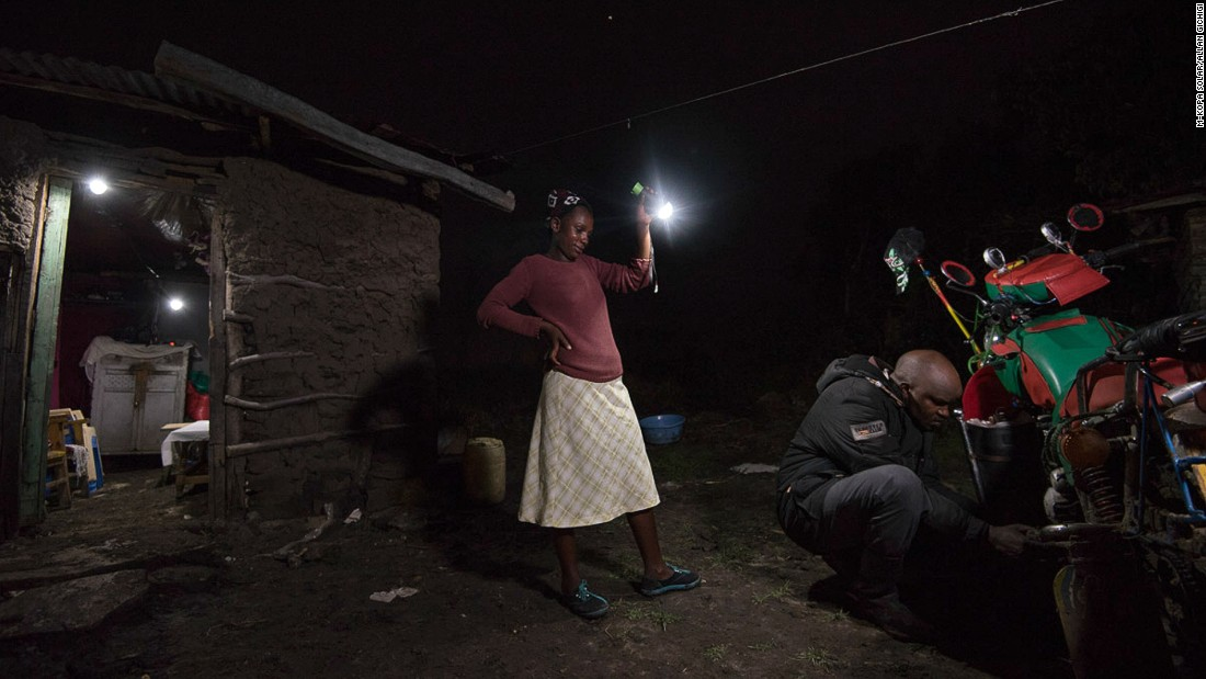 A woman lights up the compound as her husband fixes a loose screw on his motorbike. The lamp is powered by a solar panel which they have bought on M-KOPA's payment plan.