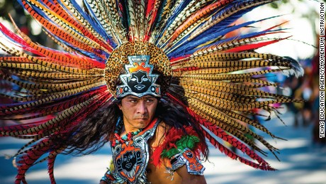 "The cover of  ""Mexican American Heritage"" features a bare-chested man with an elaborate headdress."