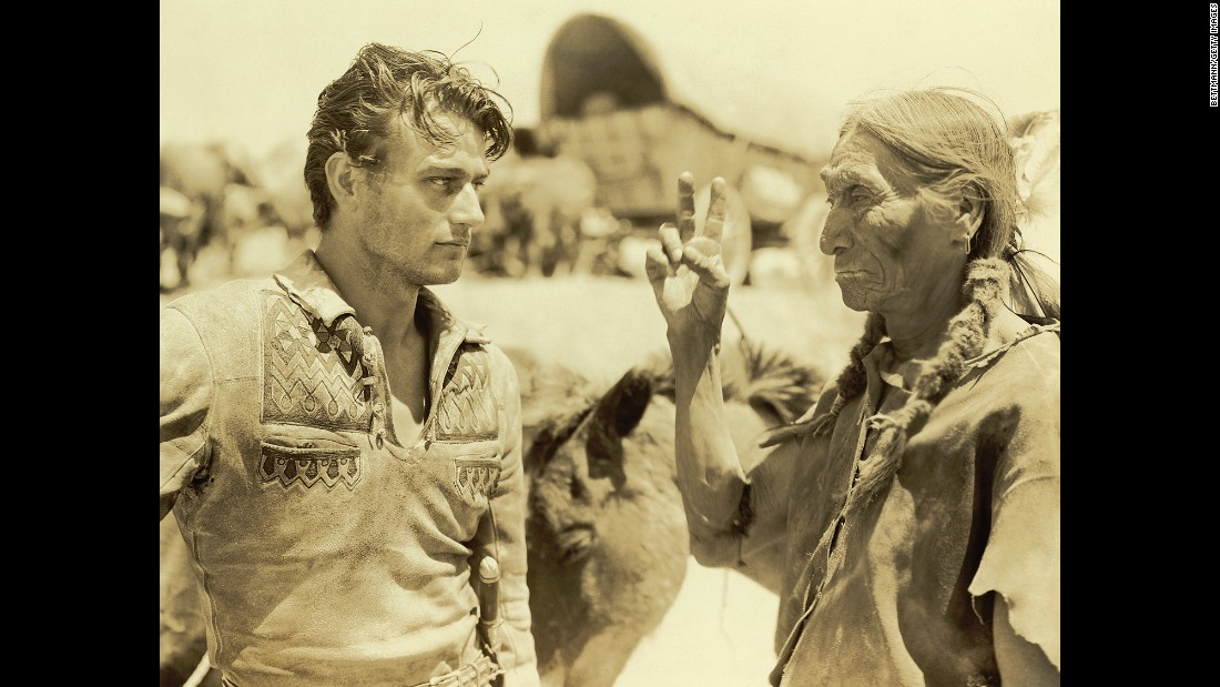 "Wayne talks to a Native American on the set of the 1930 movie ""The Big Trail."" It was Wayne's first starring role."