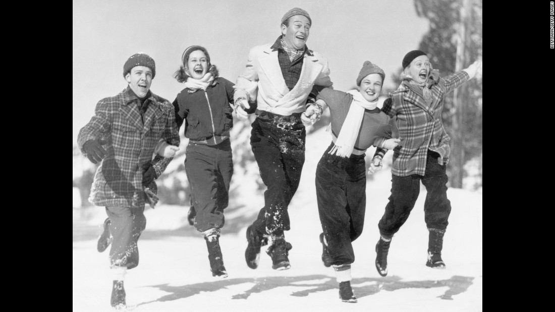Wayne and other actors from Universal Studios visit a winter resort in Big Pines, California, in 1937. From left are Michael Fitzmaurice, Barbara Read, Wayne, Fay Cotton and Emily Lane.