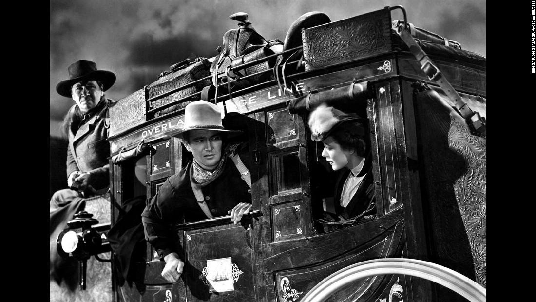 "Wayne, center, appears on the set of the 1939 film ""Stagecoach"" with George Bancroft and Louise Platt. Wayne's ""portrayals of men of duty, honor and courage, coupled with his own off-camera brand of personal true grit, endeared him to nearly three generations of Americans,"" wrote Robert Kistler of the Los Angeles Times."