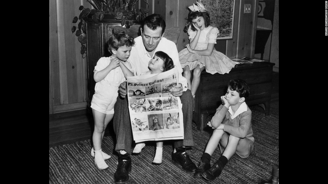 Wayne reads a comic with his four children in 1942. Wayne's children, from left, are Patrick, Melinda, Toni and Michael. He would father three more children in a later marriage.