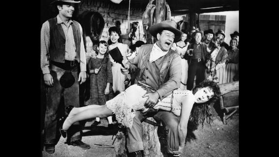 John Wayne, playing George McLintock, spanks Maureen O'Hara, playing his wife Katherine, in the Western-comedy McLintock!