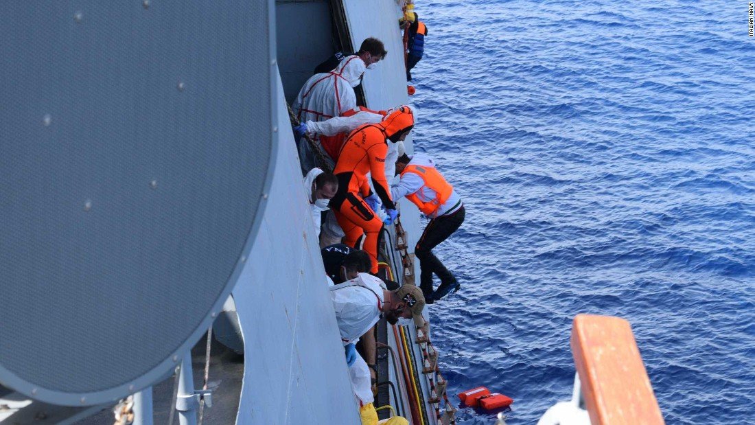 The migrants are helped on board the ship after their own vessel sank.