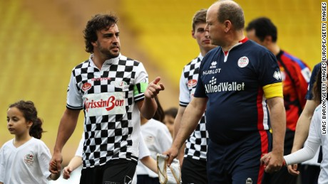 F1 star Fernando Alonso talks to Prince Albert II of Monaco as the pair lead the teams out for a charity soccer match ahead of the weekend's Monaco Grand Prix.