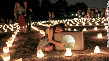 "BERLIN, GERMANY - AUGUST 13:  A visitor from Argentinia lies beside a suitcase during performances in a labyrinth of 3,000 candles at Tempelhof park (Tempelhofer Feld) on August 13, 2015 in Berlin, Germany. The maze, called ""Die Grosse Reise"" (""The Big Trip""), was opened to the public today by the theater group Theater Anu & Magica and will run through August 23.  (Photo by Carsten Koall/Getty Images)"