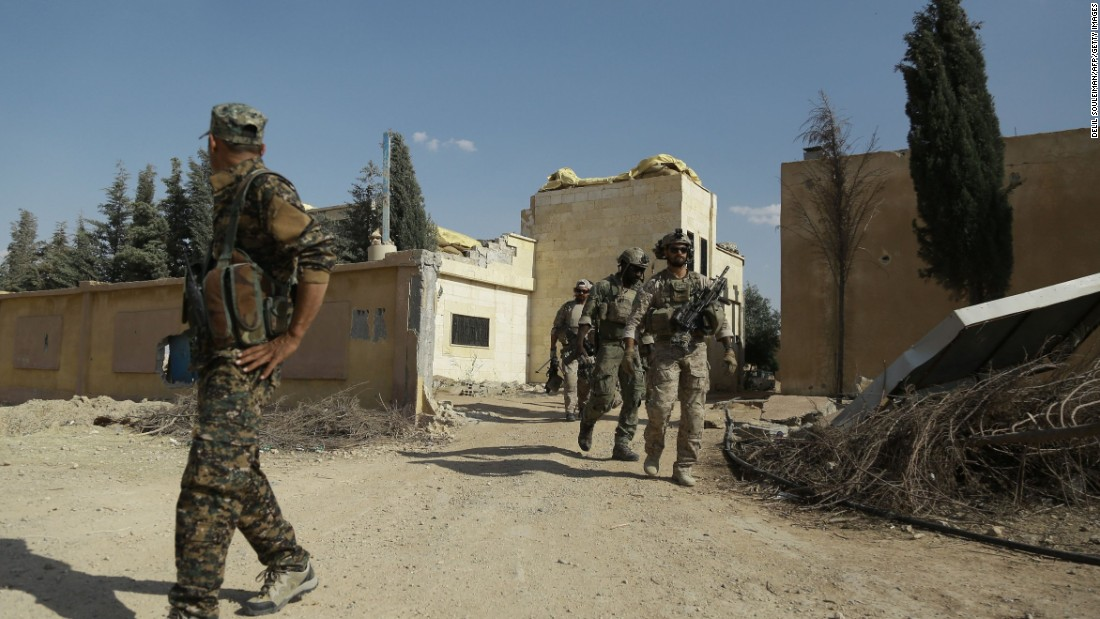 Armed men in uniform (R) identified by Syrian Democratic forces as U.S. special operations forces walk in the village of Fatisah in the northern Syrian province of Raqqa on May 25, 2016. U.S.-backed Syrian fighters and Iraqi forces pressed twin assaults against the Islamic State group, in two of the most important ground offensives yet against the jihadists.