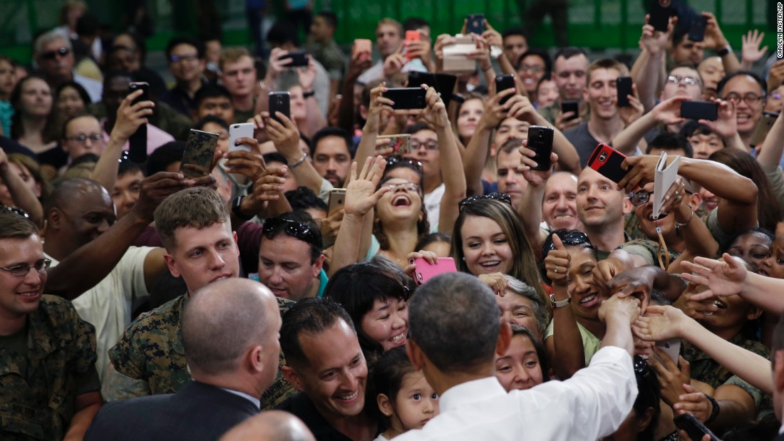 U.S. President Barack Obama, foreground center, is greeted by U.S. Marines and their families at Iwakuni air station.