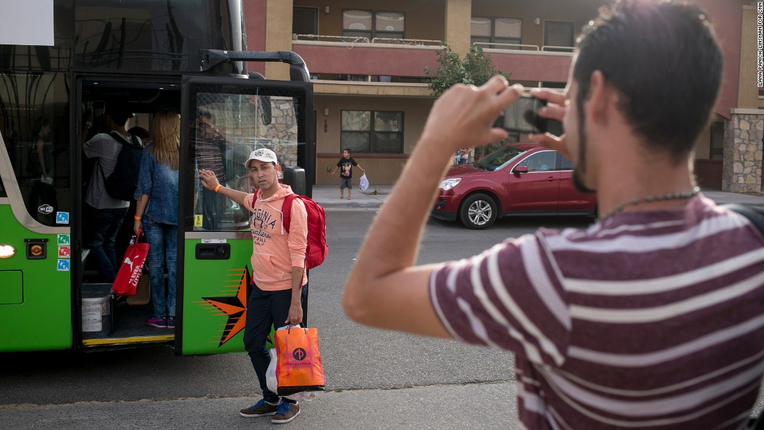 Yordanis Garcia Milian, 28, snaps a photo of his brother, Yani Garcia Milian, 38, as they prepare to board a bus in El Paso and begin their journey to meet family in Melbourne, Florida.